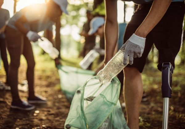 Group of multi-ethnic people, people with differing abilities , volunteers with garbage bags cleaning park area